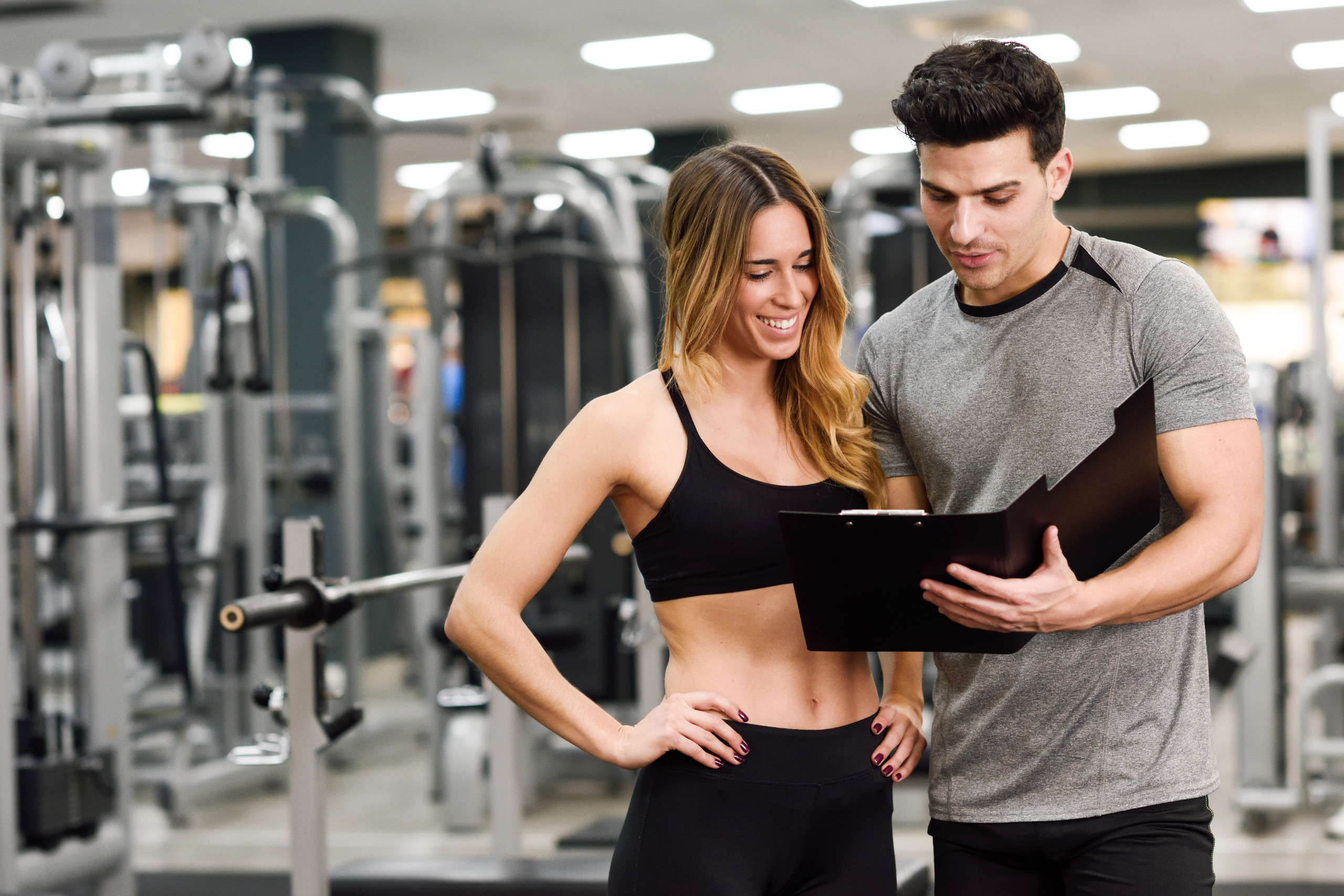 Personal trainer and client looking at her progress at the gym. Athletic man and woman wearing sportswear.